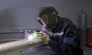 An image of a man using a welding machine